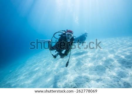 Scuba Diver passing through sandy bottom tropical sea. #262778069