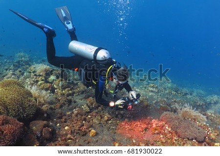 Scuba diver photographer swimming underwater on the beautiful coral reef. Colorful tropical reef landscape with deep blue water and scuba diver. Fish, corals and water plants. #681930022