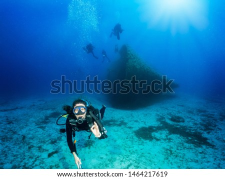 Scuba diver shows the OK sign under water during a deep wreck dive in the blue, Aegean Sea in Greece #1464217619