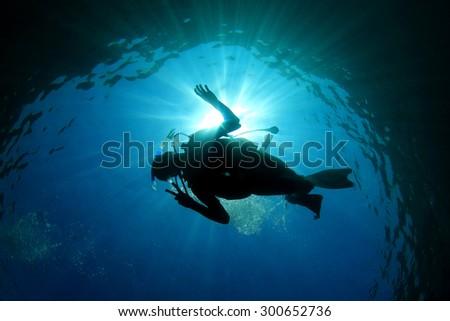 Scuba diver silhouette and sun #300652736