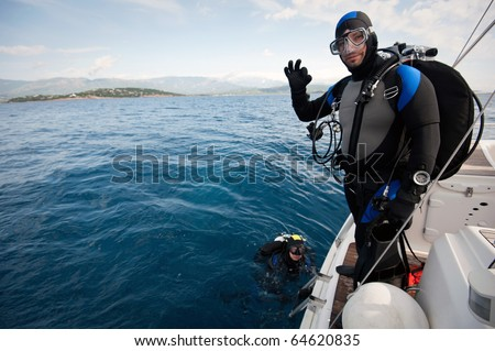 scuba diver standing on the yacht and ready to dive