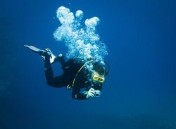 Scuba diver taking underwater photo in deep blue water