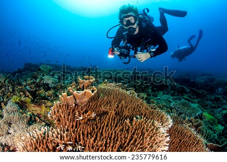 SCUBA diver with a camera swims over a colorful tropical coral reef #235779616