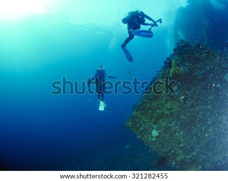 Scuba diver with a camera swims over a colorful tropical coral reef. #321282455