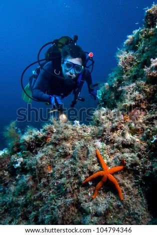 Scuba diver with red starfish - stock photo