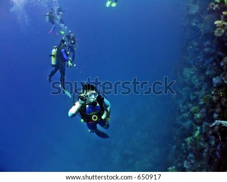 Scuba divers beginning to dive the Wall, on the Great Barrier Reef - stock photo