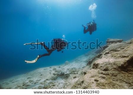 Scuba divers diving underwater. Two scuba divers  #1314403940