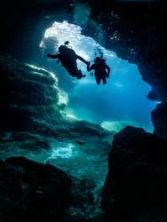 scuba divers entering a cave
