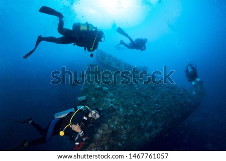 Scuba divers explore crashed prow of shipwreck. Red sea, Egypt.  #1467761057