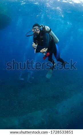 Scuba divers explore shipwreck. Red sea, Egypt. Сток-фото ©