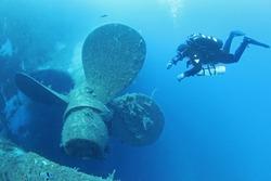 Scuba divers explores propeller of sunken shipwreck Zenobia, Cyprus.