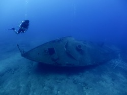 scuba divers exploring and discovering the ship wreck underwater deep sea bottom