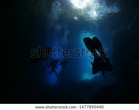 scuba divers exploring the caves underwater cave diving with blue water #1477890440