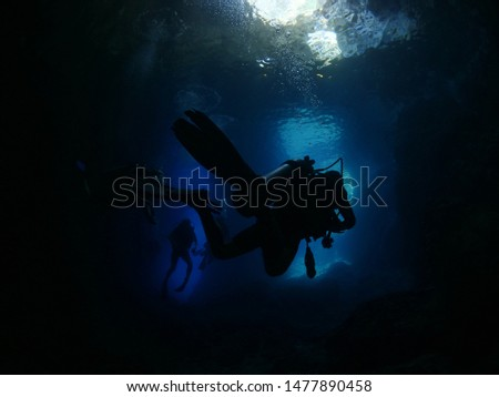 scuba divers exploring the caves underwater cave diving with blue water #1477890458