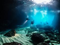 scuba divers exporing underwater caves