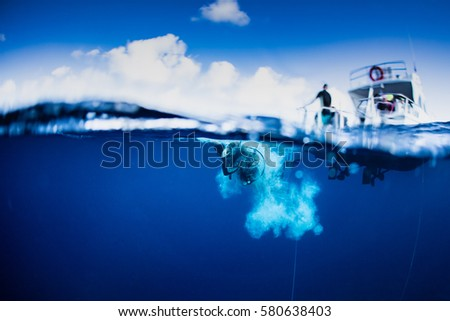 scuba divers in crystal clear caribbean water jumping off the back of a dive boat, surrounded in bubbles.  #580638403