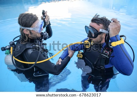 Scuba divers learning how to dive in a swimming pool #678623017