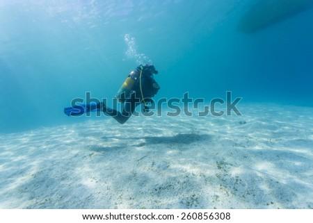 Scuba Divers passing through sandy bottom tropical sea. #260856308