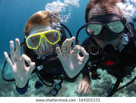 Scuba divers showing OK signal underwater
