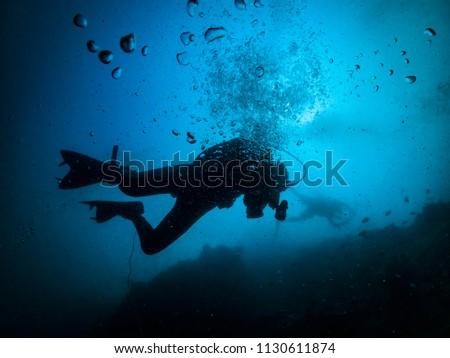 scuba divers silhouette with bubble in a blue sea #1130611874