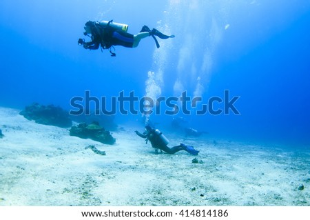Scuba divers swim over colorful tropical coral reef #414814186