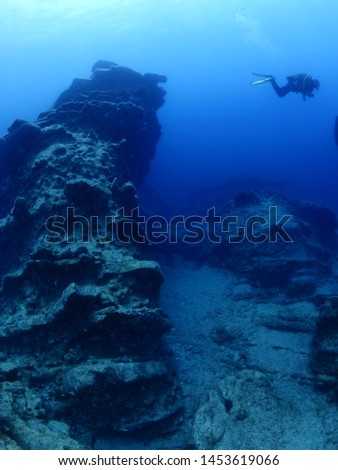 scuba divers underwater exploring and siscovering the strange shape rocks underwater #1453619066