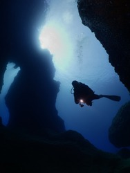 Scuba divers underwater exploring caves blue ocean scenery with torch light