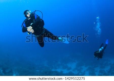 Scuba divers underwater in the deep blue ocean. #1429512275