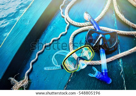 Scuba diving and snorkeling. Two snorkel on blue wood background. The deck and the nose of the ship with a solar glare #548805196