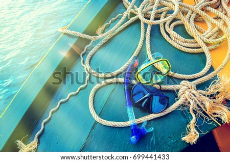 Scuba diving and snorkeling. Two snorkel on blue wood Ship deck. The deck and the ship's bow. Sea trips to the islands, swimming with fish. The concept of sea voyage #699441433