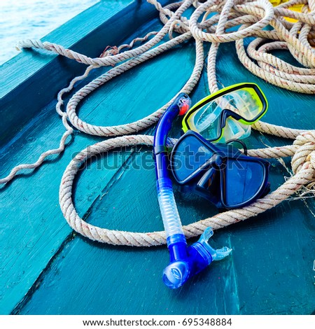 Scuba diving and snorkeling. Two snorkel on blue wood Ship deck. The deck and the ship's bow. The concept of sea voyage #695348884