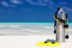 Scuba diving equipment on a tropical beach