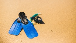 Scuba mask with fins on the beach sand. Blue flippers on the shore.