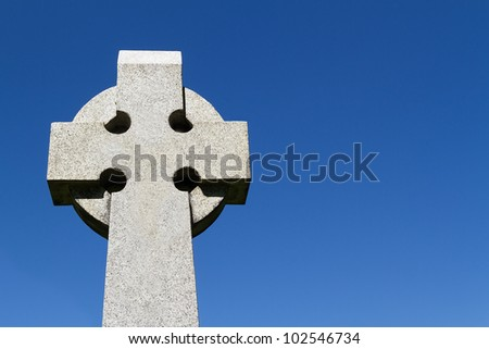 Sculpted Celtic stone cross against a deep blue sky with great text space