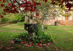 Sculpted stone surrounded by autumn foliage in the house garden
