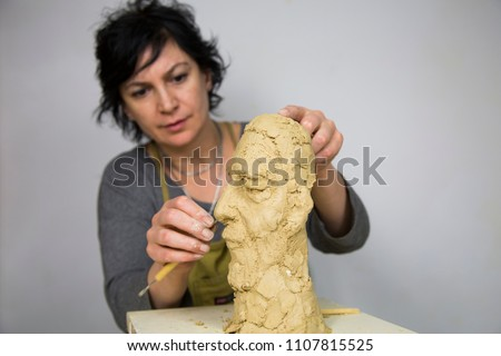 Sculptor artist creating a bust sculpture with clay. She is happy of her work, she is concentrated, she is sculpting a woman. the statue is at foreground. Sculptor at work.