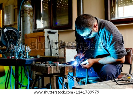Sculptor is using arc welding to assembly metal sculpture barehanded with protective spectacles.
