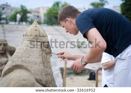 Sculptor making a sand figure of hero