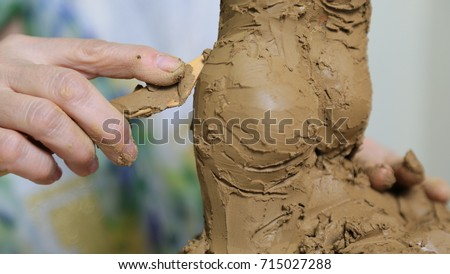 Sculptor Uses Tool To Sculpt Side Of Statue. Sculptor at work.