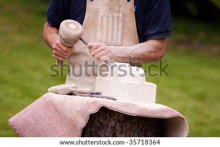 Sculptor working a block of stone with a chisel