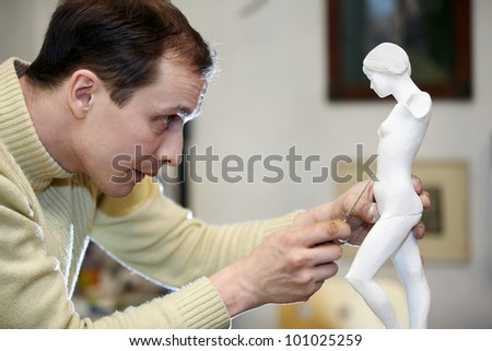 Sculptor works with concentration in the studio on a fragment of plaster sculpture.