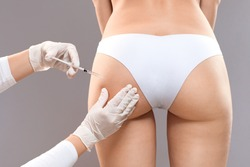 Sculptra butt lifting concept. Slim woman having hip injection at beauty salon, closeup. Plastic surgeon making injection at butt area for unrecognizable lady, grey studio background, back view