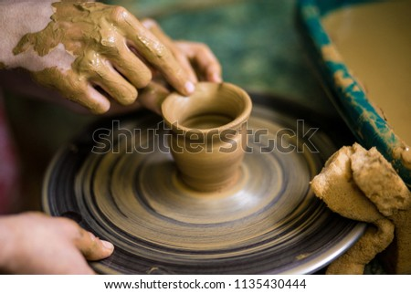 Sculpts in clay pot closeup. Modeling clay close-up. Caucasian man making vessel daytime of white clay in fast moving circle. Art, creativity. Ukraine, cultural traditions. Hobbies #1135430444