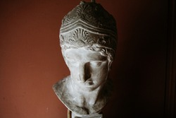 sculptural female head in a museum on a red background