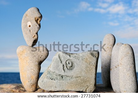 Sculptural group of stone idols on the shore of ocean