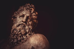 Sculptural portrait of an antique man with a bushy beard. Sculptural portrait of a man with a beard made of marble. Bust of a man in marble against the background of a burgundy wall.