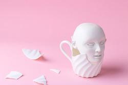 Sculpture head in broken cup, concept
