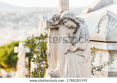 sculpture of a angel with a cross at old cemetery. Closeup of stoned angel with crying at cemetery. Graveyard old weathered stone sad statue on funeral. black and white. Foto stock ©