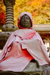 Sculpture of a japanese monk wearing a red raincoat in a shrine in Yamadera, Yamagata