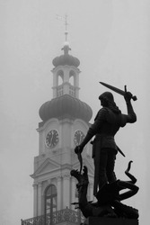 Sculpture of a knight with sword and dragon against a background of the city hall clock tower in Riga on a foggy day. monochrome